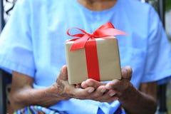 Manos del hombre mayor que sostienen la caja de regalo con la cinta roja para el día de la Navidad y de Año Nuevo o que saludan l imagenes de archivo