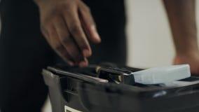 Manos del hombre negro que abren la caja de herramientas Manos masculinas del primer que toman el destornillador almacen de metraje de vídeo
