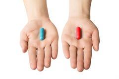 Manos del hombre que dan dos píldoras grandes Azul y rojo Haga su selección Salud o enfermedad Elija su lado Imagenes de archivo