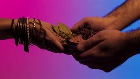 Manos del hombre que dan una placa del sistema de la especia a las manos indias de la mujer, aislada en fondo azul y rosado exist imagen de archivo libre de regalías