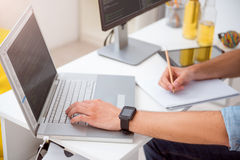 Manos del hombre que golpean ligeramente en el ordenador portátil imagen de archivo libre de regalías