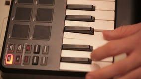 Manos del hombre que juegan un sintetizador del teclado del controlador midi almacen de video