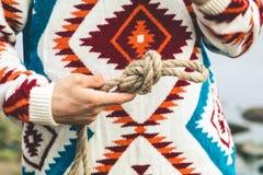 Manos del hombre que llevan a cabo forma de vida del viaje del nudo de la cuerda Fotos de archivo libres de regalías