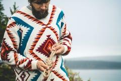 Manos del hombre que llevan a cabo forma de vida del viaje del nudo de la cuerda Foto de archivo
