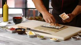 Manos del hombre que preparan el sushi
