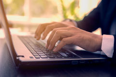 Manos del hombre que pulsan en el teclado de la computadora portátil Imagenes de archivo