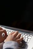 Manos del hombre que pulsan en la computadora portátil Imágenes de archivo libres de regalías