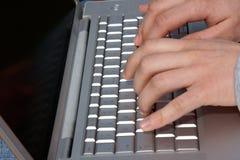 Manos del hombre que pulsan en la computadora portátil Imagenes de archivo