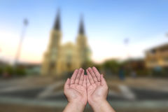 Manos del hombre que ruegan bendiciones borrosas delante de la iglesia Fotos de archivo libres de regalías