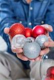 Manos del hombre que sostienen bolas coloridas de la Navidad Imagen de archivo