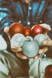 Manos del hombre que sostienen bolas coloridas de la Navidad Fotos de archivo libres de regalías