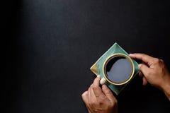 Manos del hombre que sostienen el café en la tabla de cocina Imagen de archivo