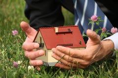Manos del hombre que sostienen la miniatura de la casa, collage imagen de archivo