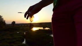 Manos del hombre que sostienen las gafas de sol en la puesta del sol metrajes