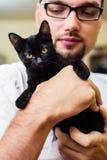 Manos del hombre que sostienen un gato negro del bebé Fotografía de archivo