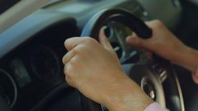 Manos del hombre que sostienen un volante con confianza almacen de metraje de vídeo