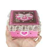 Manos del hombre que sostienen una caja de regalo rosada Imagen de archivo libre de regalías