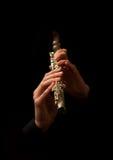 Manos del hombre que tocan una flauta Imagenes de archivo