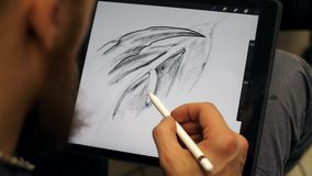 Manos del hombre que trabajan en la tableta gráfica El diseñador trabaja en la tableta gráfica en la PC metrajes