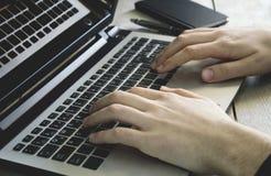 Manos del hombre usando el ordenador portátil en fondo de madera fotografía de archivo libre de regalías