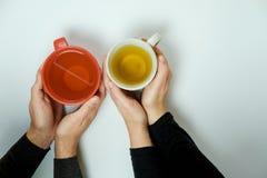 Manos del hombre y de la mujer con las tazas de té en el fondo blanco Imágenes de archivo libres de regalías