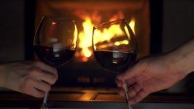 Manos del hombre y de la mujer del primer que tuestan los vidrios del tintineo con la chimenea del vino tinto en fondo metrajes