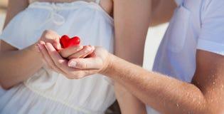 Manos del hombre y de la mujer que llevan a cabo el corazón rojo Fotos de archivo libres de regalías