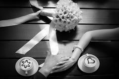 Manos del hombre y de la mujer y tazas de café en la tabla Fotos de archivo