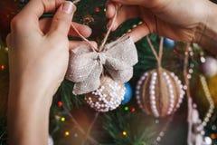 Manos del inconformista con la bola y el arco de la harpillera de la Navidad Imagen de archivo libre de regalías