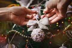 Manos del inconformista con la bola y el arco de la Navidad Fotos de archivo libres de regalías