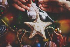 Manos del inconformista con la estrella de la harpillera de la Navidad Imagenes de archivo