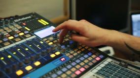 Manos del ingeniero audio que trabajan en una consola análoga profesional, música de mezcla almacen de metraje de vídeo