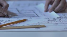 Manos del ingeniero que dibujan la nueva disposición del edificio, oficina del diseño de la arquitectura almacen de video