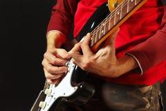Manos del músico de la roca que tocan la guitarra eléctrica en fondo negro Fotos de archivo libres de regalías