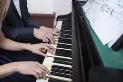 Manos del músico del primer que juegan el piano en el teclado de piano foto de archivo