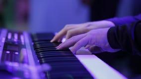 Manos del músico que juegan el teclado conjuntamente con la profundidad del campo baja metrajes