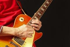 Manos del músico que tocan la guitarra eléctrica en fondo oscuro Imagenes de archivo