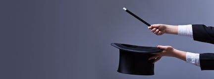 Manos del mago con el sombrero y la vara de la magia Fotos de archivo