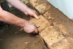 Manos del masón en los trabajos de la levantamiento de muros imagen de archivo