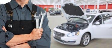 Manos del mecánico de coche con la llave imagen de archivo