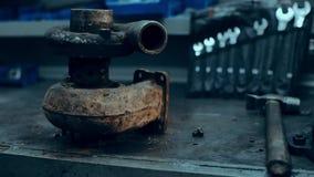 Manos del mecánico de coche en garaje con el turbocompresor viejo y usado Concepto de la turbina almacen de metraje de vídeo