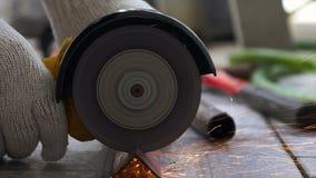 Manos del mecánico que usa la amoladora eléctrica a cortar el acero con el parpadeo de la luz del fuego almacen de metraje de vídeo