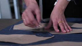 Manos del modelo de trazado del sastre de sexo femenino en tela metrajes