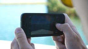Manos del muchacho joven que usa smartphone a tomar la foto del barco flotante en la bahía hermosa en el día soleado Navegación t almacen de video