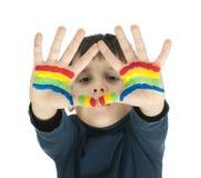 Manos del muchacho pintadas con la pintura colorida Fotos de archivo