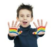 Manos del muchacho pintadas con la pintura colorida Fotografía de archivo libre de regalías