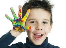 Manos del muchacho pintadas con la pintura colorida Foto de archivo