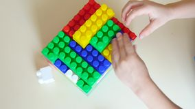 Manos del muchacho que juegan con los bloques del color metrajes