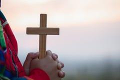 Manos del muchacho que llevan a cabo una cruz santa y que ruegan a dios, niño que ruega para la religión de dios imagen de archivo