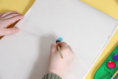 Manos del muchacho que pintan en la tablilla foto de archivo libre de regalías